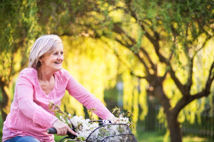 woman cycling outside in spring nature.
