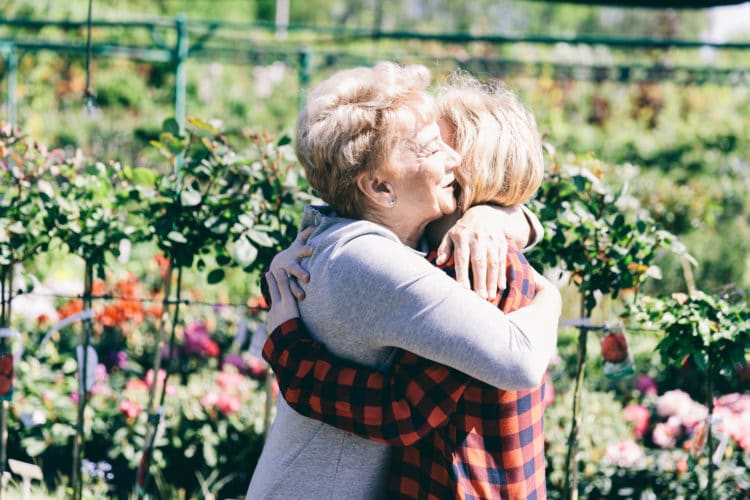 Older lady hugging her granddaughter in a garden. Family love and generations concept.