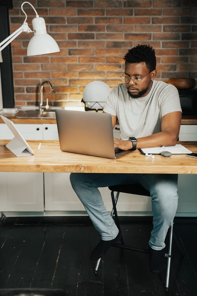 Career in marketing: Man at home sitting at a desk working on his laptop